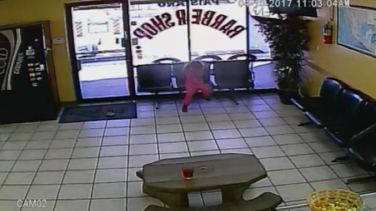A little girl covers her face as bullets fly through a window shes sitting by at an Arizona barbershop.