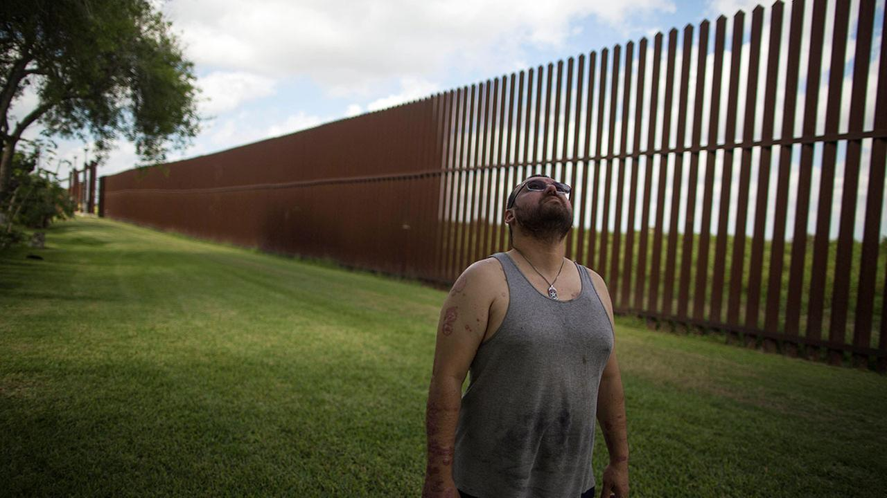 Antonio Reyes stands by the U.S.-Mexico border fence near his home in Brownsville, Texas.