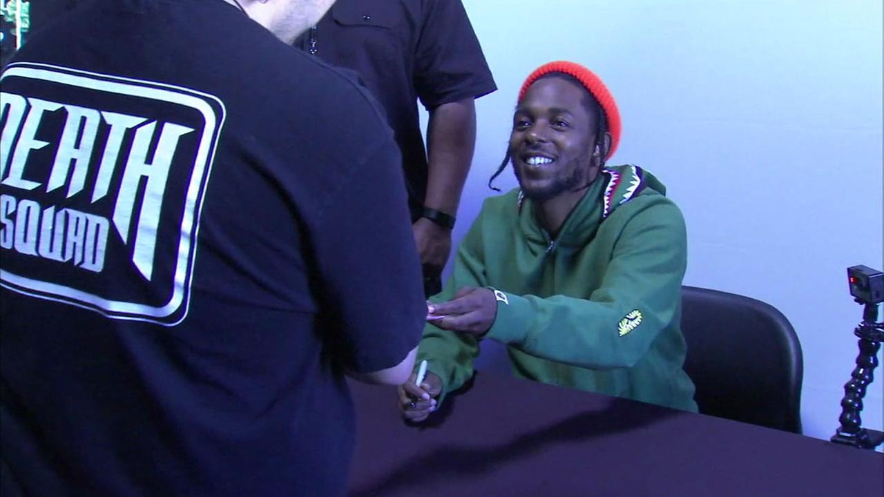 Rapper and Compton native Kendrick Lamar is shown signing copies of his new album, Damn, at a Best Buy on Thursday, April 20, 2017.
