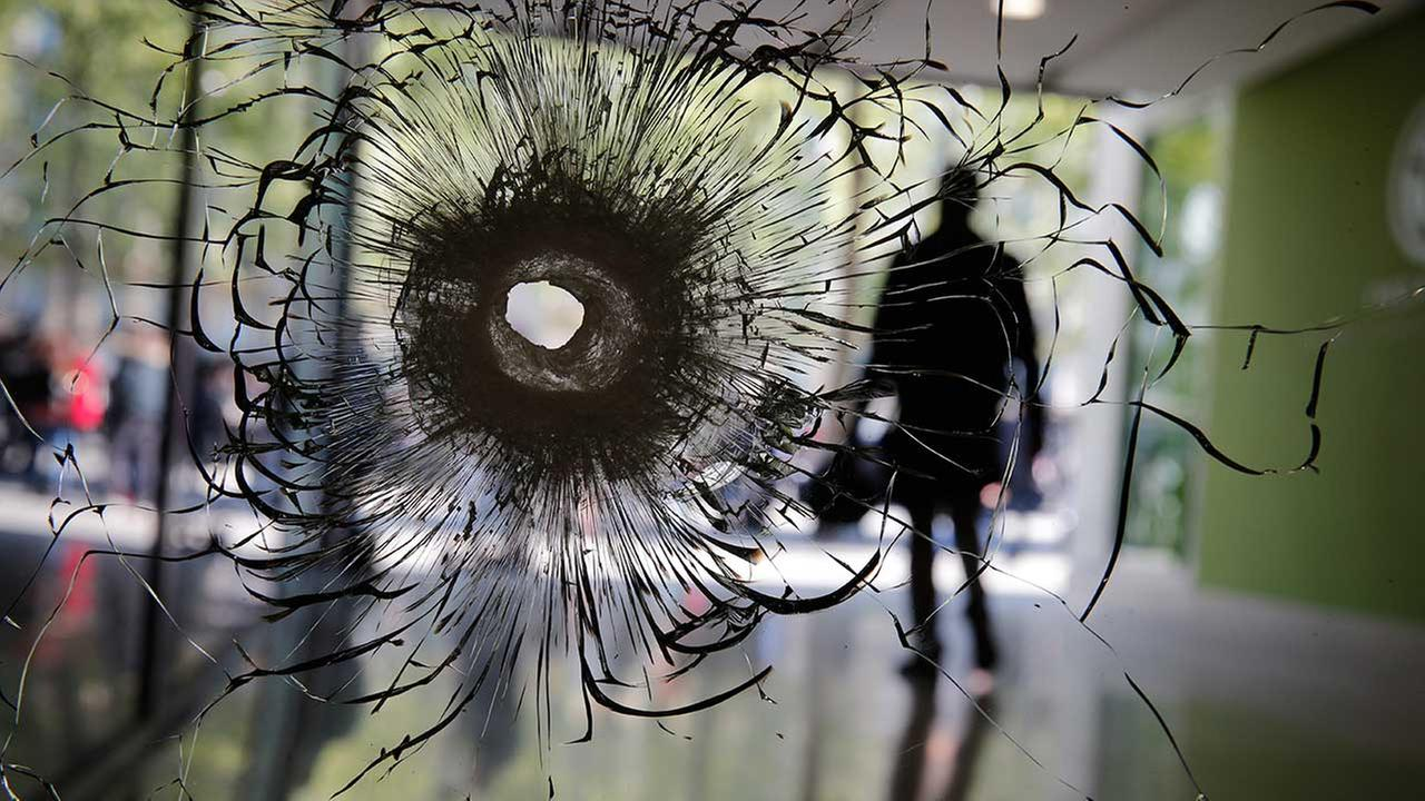 A bullet hole is pictured on a shopwindow of the Champs-Elysees boulevard in Paris, Friday, April 21, 2017. (AP Photo/Christophe Ena)