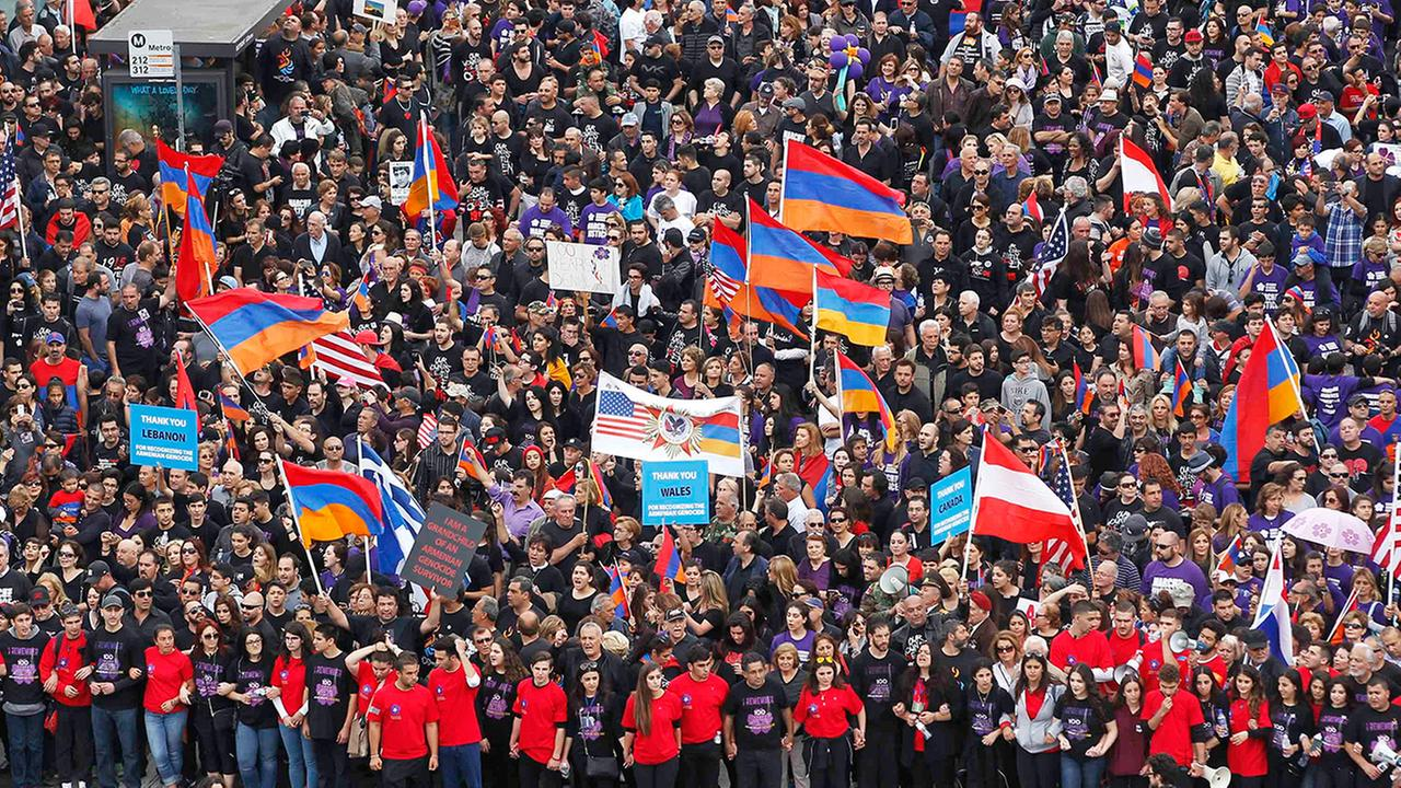 Some of tens of thousands of demonstrators carrying signs and Armenian flags march down La Brea Avenue in Los Angeles Friday, April 24, 2015.