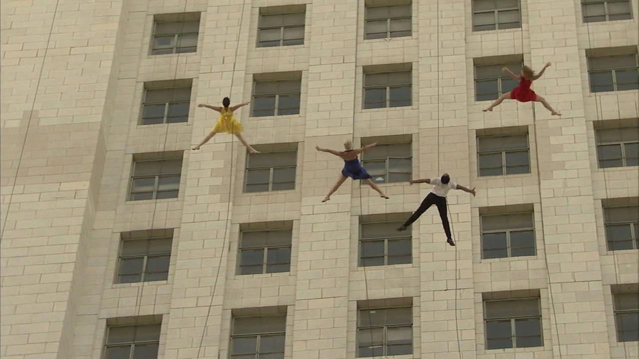 Acrobats suspended from ropes performed along the side of Los Angeles City Hall as the city declared Tuesday La La Land day.