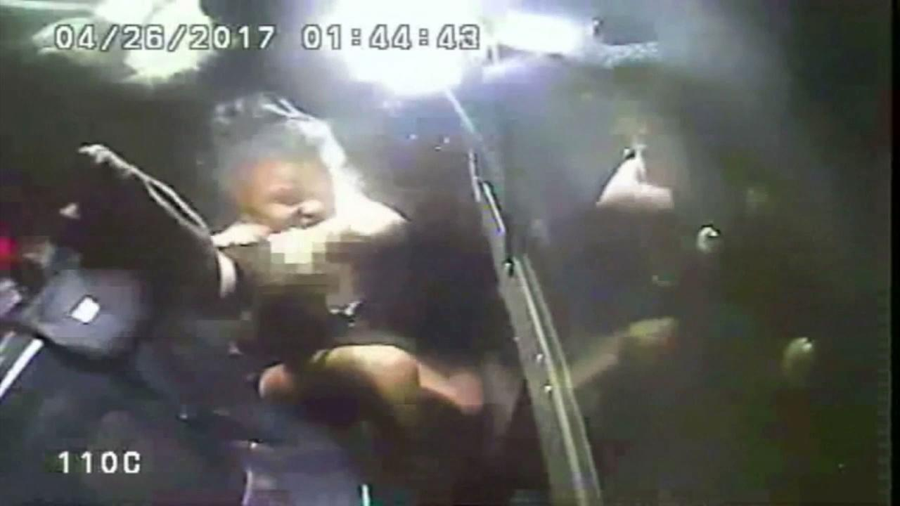 Police video shows an Ohio woman with her dress falling off in the back of a police cruiser as she tried to spray officers with mace and gets sprayed back.