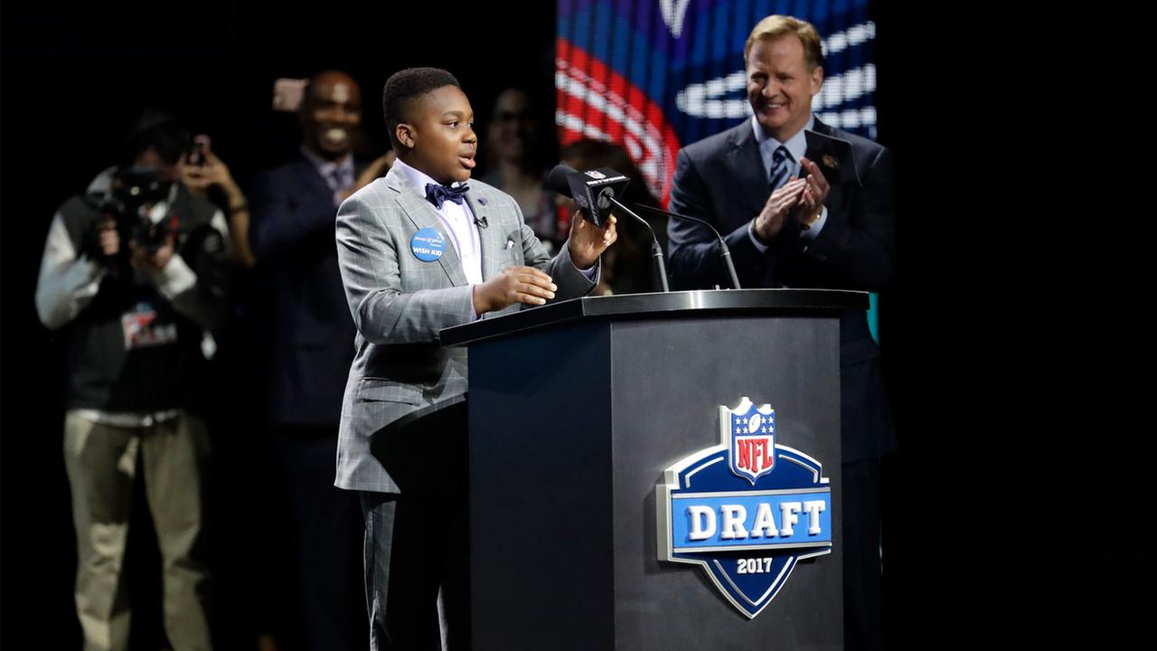 T.J. Owuanibe, 14, announces the Baltimore Ravens selection during the first round of the 2017 NFL football draft, Thursday, April 27, 2017, in Philadelphia.