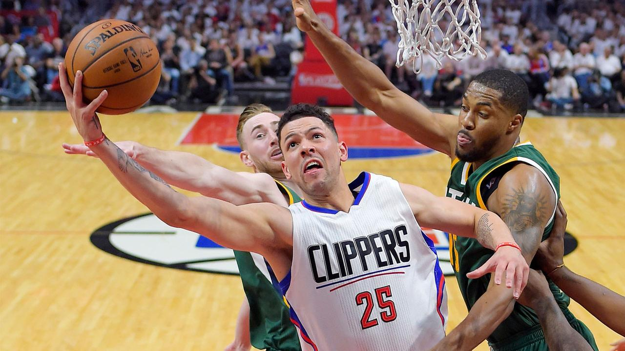 Los Angeles Clippers guard Austin Rivers, center, shoots as Utah Jazz forward Gordon Hayward, left, and forward Derrick Favors defend during the first half in Game 7.