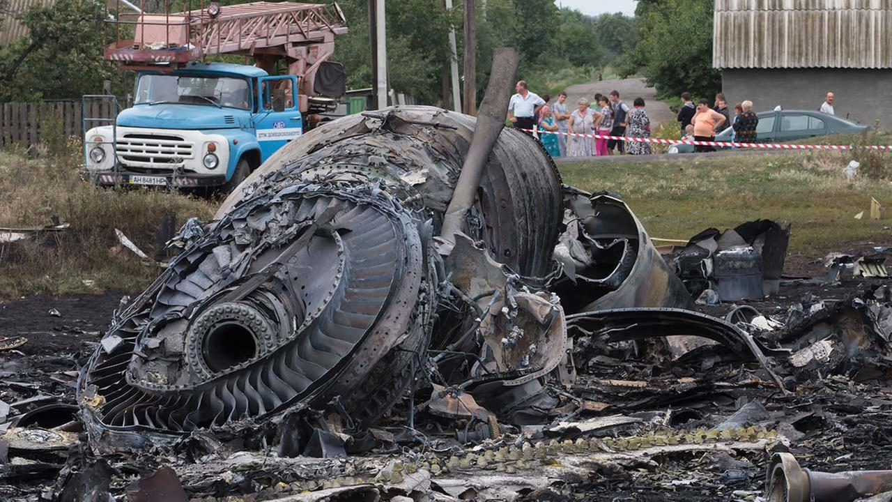 Local citizens, background, look at the site of a crashed Malaysia Airlines passenger plane in eastern Ukraine Friday, July 18, 2014.