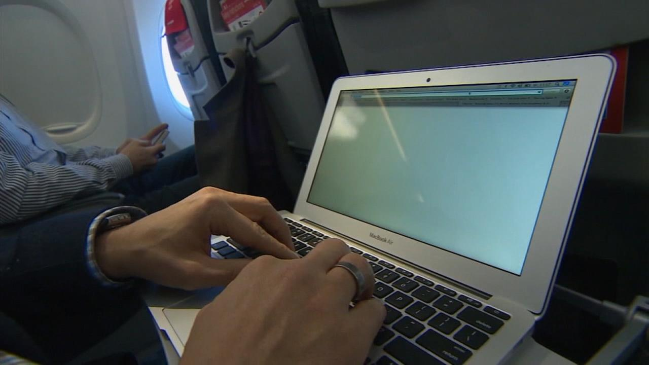 A passenger uses a laptop aboard a commercial plane in an undated file photo.