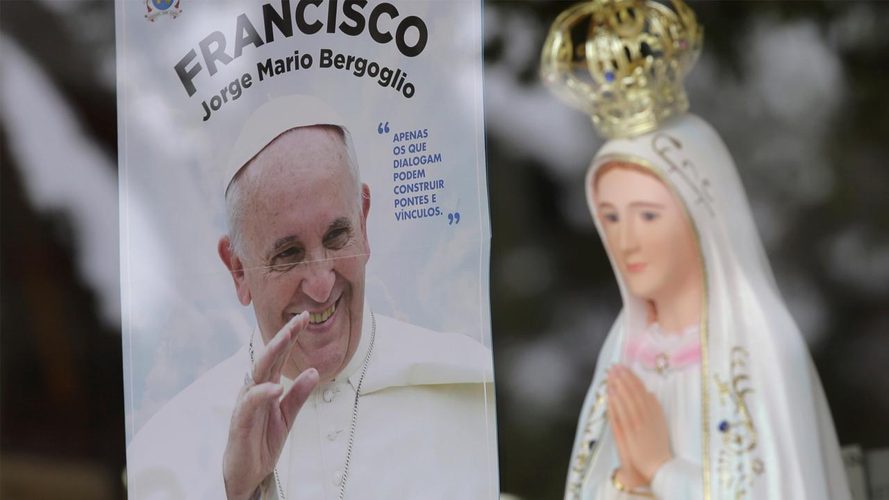In this photo taken May 4, 2017, a photograph of Pope Francis, Francisco in Portuguese, is displayed in the window of a shop selling statues of Our Lady of Fatima, in  Portugal.