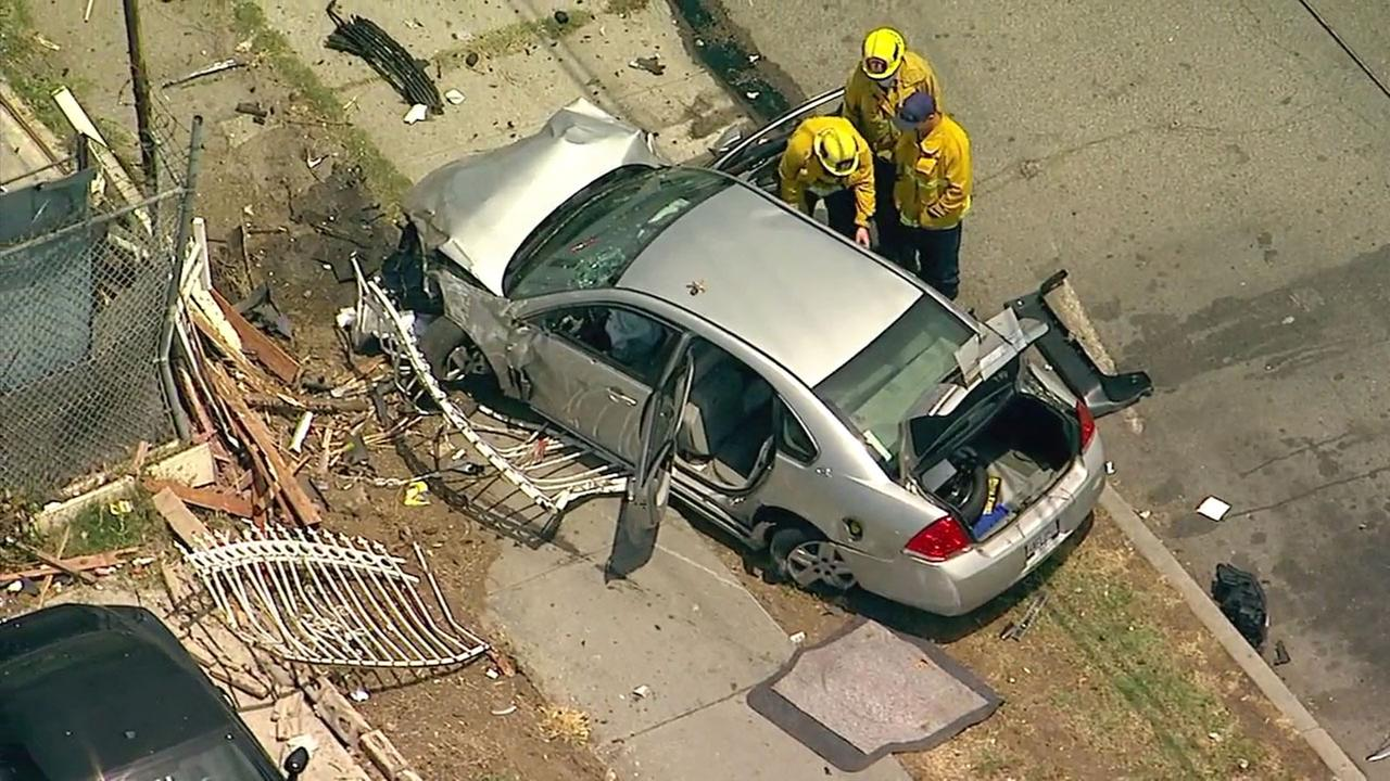 Officials investigate a vehicle that crashed at the end of a chase in South Los Angeles.
