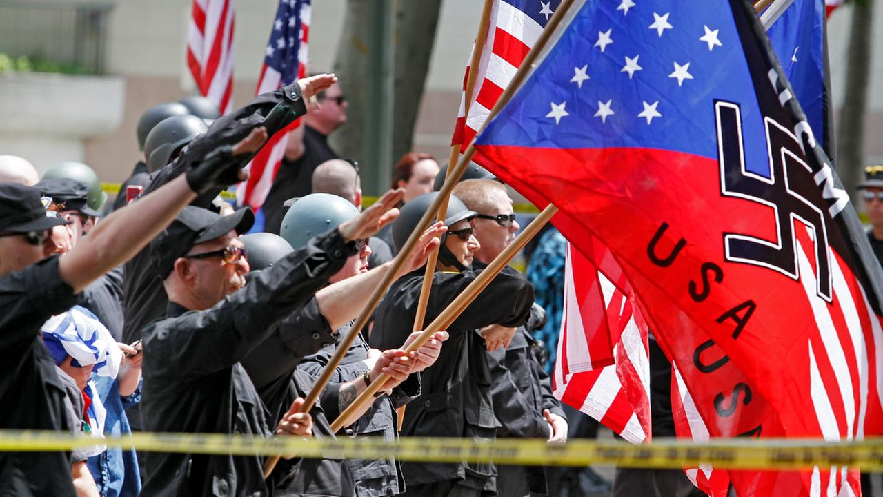 A white supremacist group salutes American flags and banners with swastikas at Los Angeles City Hall on Saturday, April 17, 2010.