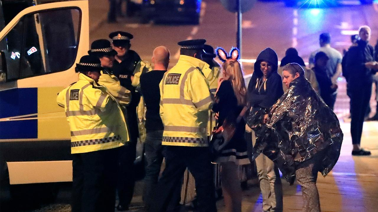 Emergency services personnel speak to people outside Manchester Arena after reports of an explosion at the venue during an Ariana Grande concert in Manchester, England.