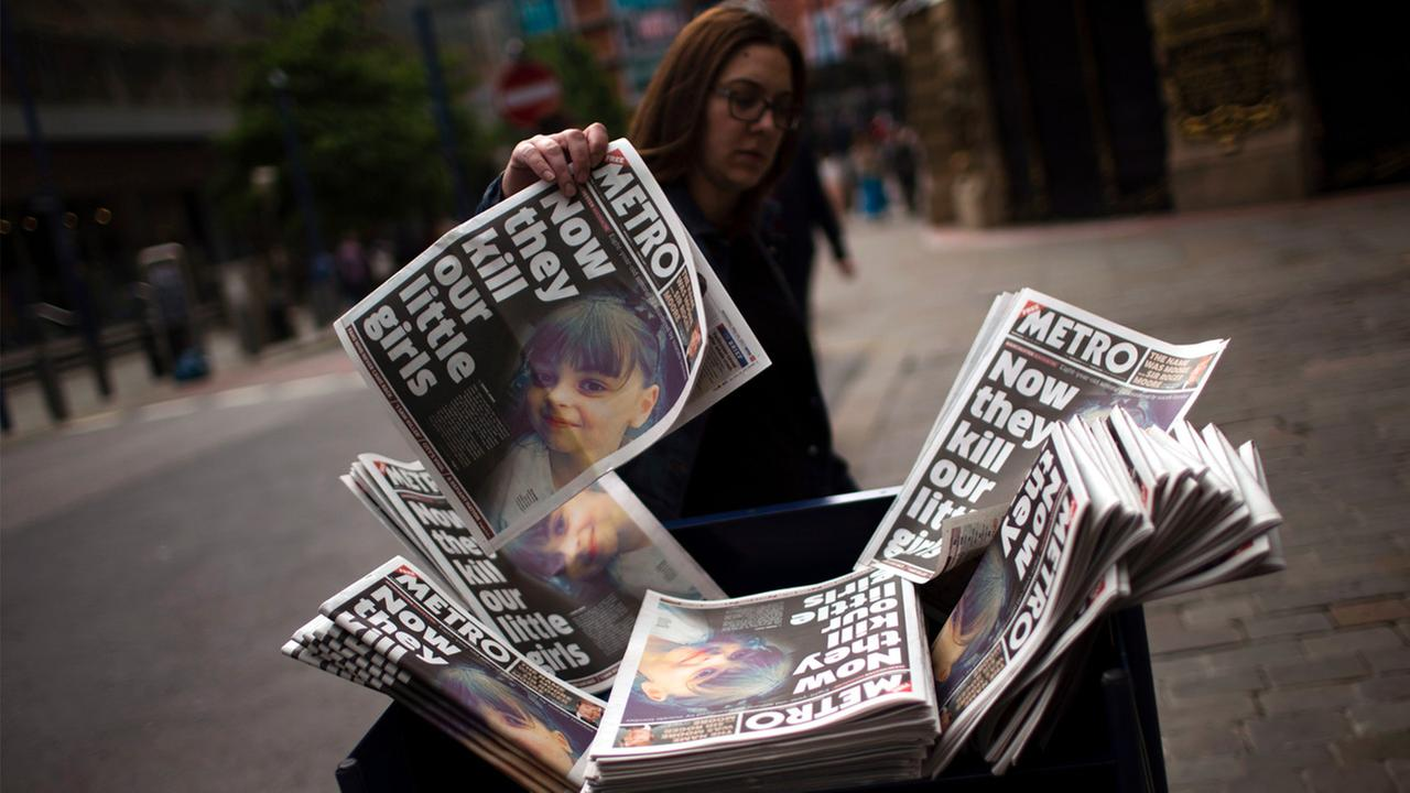 A woman picks a newspaper reporting the news on the suicide attack at a concert by Ariana Grande that killed more than 20 people as it ended Monday night in central Manchester.
