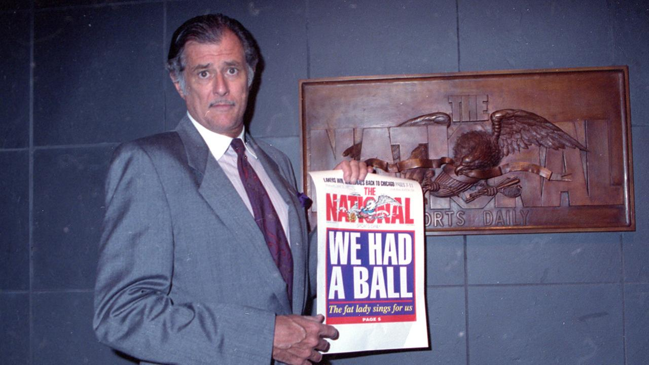 Frank Deford holds a proof of the final front page of the newspaper after a news conference at the papers offices in New York City on Wednesday, June 12, 1991.