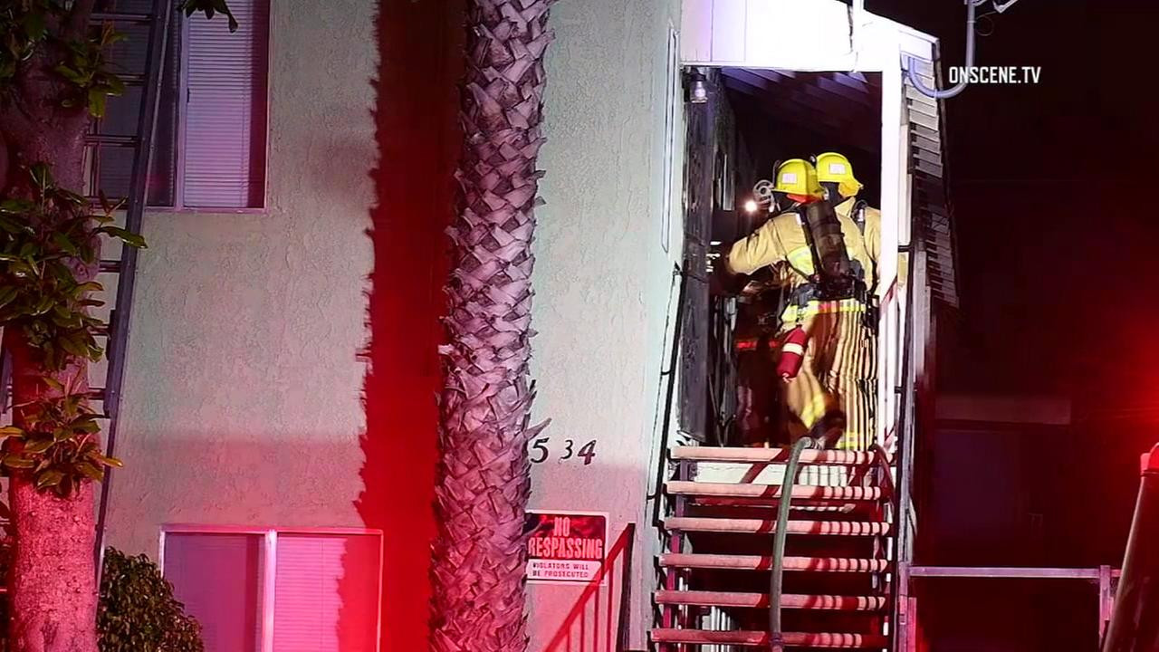 Firefighters make entry into a Long Beach apartment, where the body of a man was discovered during a fire on Tuesday, May 30, 2017.