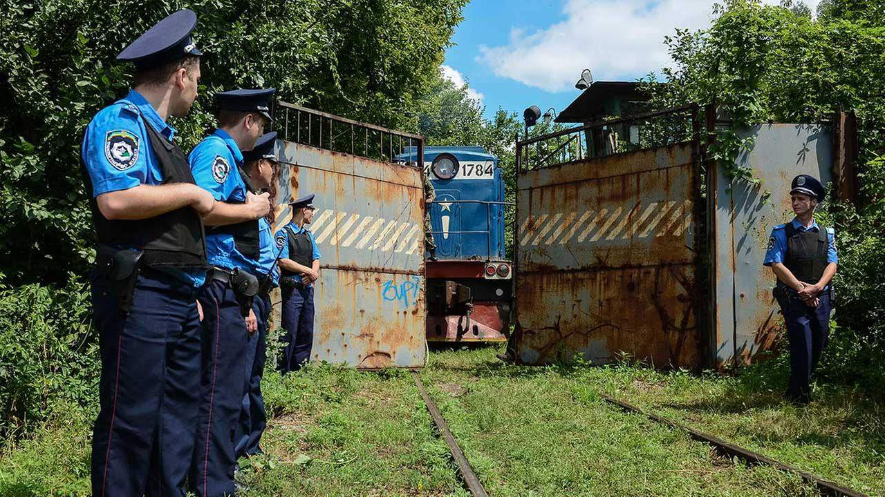 Police officers secure a refrigerated train loaded with bodies of the passengers of Malaysian Airlines Flight MH17 as it arrives in a Kharkiv factory for a stop on July 22, 2014.