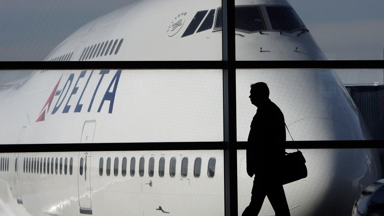 In this file photo made Jan. 21, 2010, a passenger walks past a Delta Airlines 747 aircraft in McNamara Terminal at Detroit Metropolitan Wayne County Airport in Romulus, Mich.