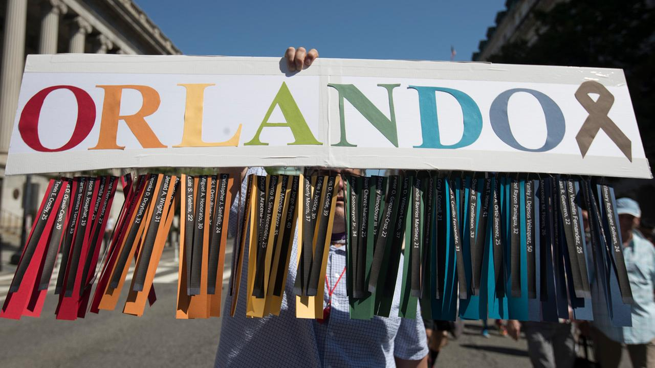 Gil Mendez, of San Francisco, holds a sign to honor the victims of the shooting at the Pulse Nightclub in Orlando, Fla.