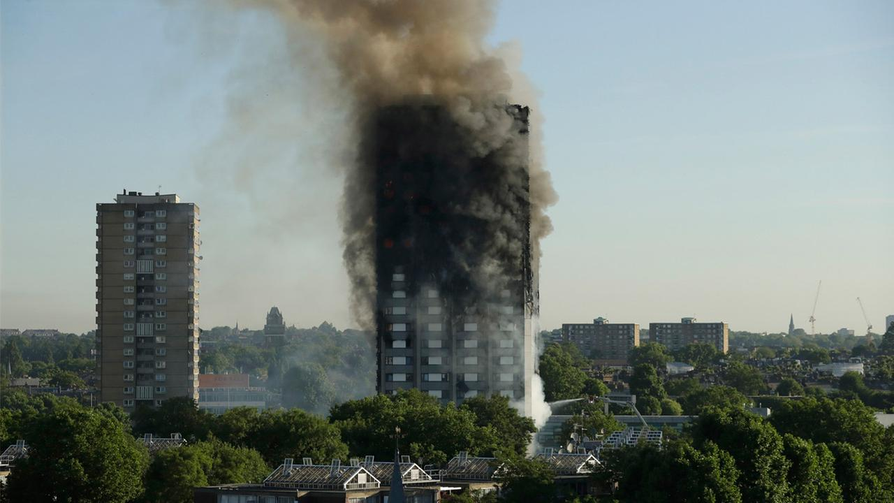 Smoke rises from a building on fire in London, Wednesday, June 14, 2017. A massive fire raced through the 27-story high-rise apartment building in west London early Wednesday.
