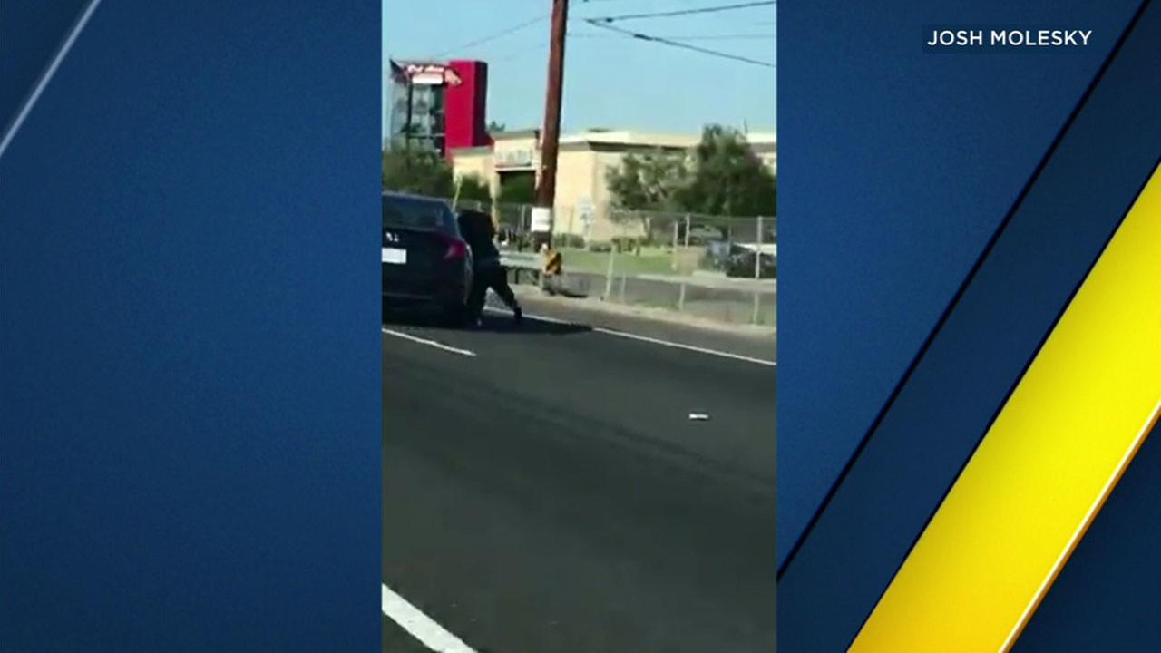 VIDEO: Woman holds onto car as it travels on 55 Fwy in OC in apparent road rage incident