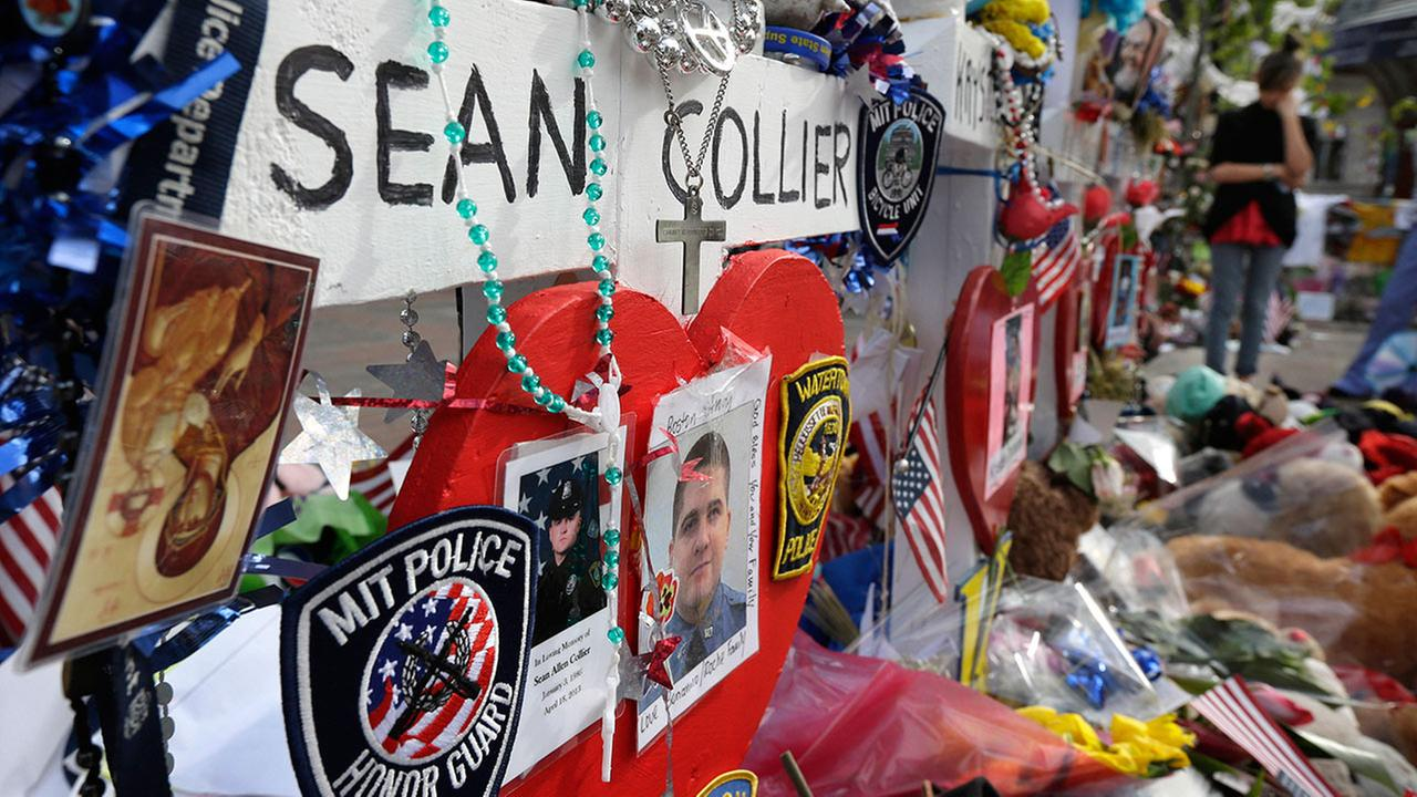 Photographs of slain Massachusetts Institute of Technology campus officer Sean Collier, center, are part of a makeshift memorial near the Boston Marathon finish line in Bostons Copley Square Tuesday, May 7, 2013.