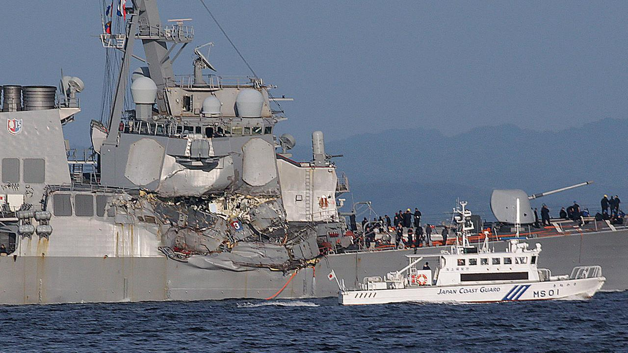 A Japan Coast Guard ship, foreground, navigates the damaged USS Fitzgerald near the U.S. Naval base in Yokosuka, southwest of Tokyo.