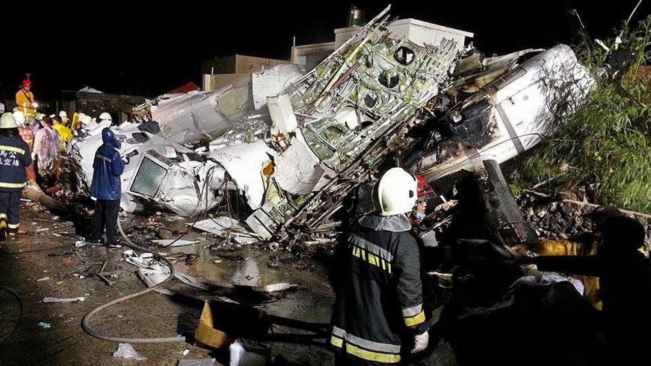 Rescue workers survey the wreckage of TransAsia Airways flight GE222 which crashed while attempting to land in stormy weather on the Taiwanese island of Penghu July 23, 2014.