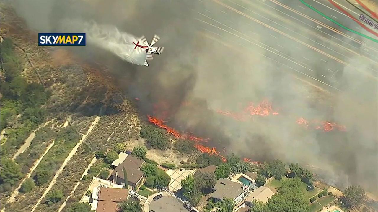 A brush fire in the Santa Clarita area approaches homes on Sunday, June 25, 2017.
