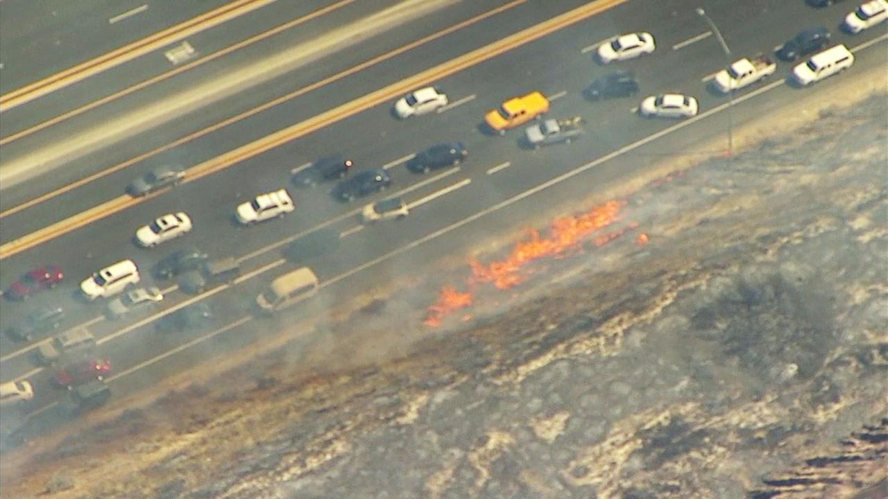 Part of the Placerita Fire burns near cars along the 14 Freeway on Sunday, June 25, 2017.