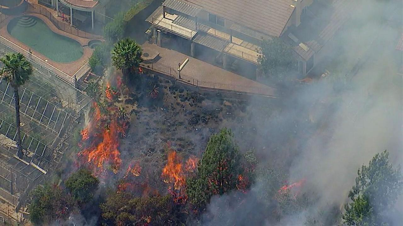 Flames eat up dry brush near a home in Burbank on Wednesday, June 28, 2017.KABC