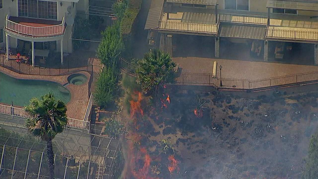 Flames burn a tree near a home in Burbank on Wednesday, June 28, 2017.KABC