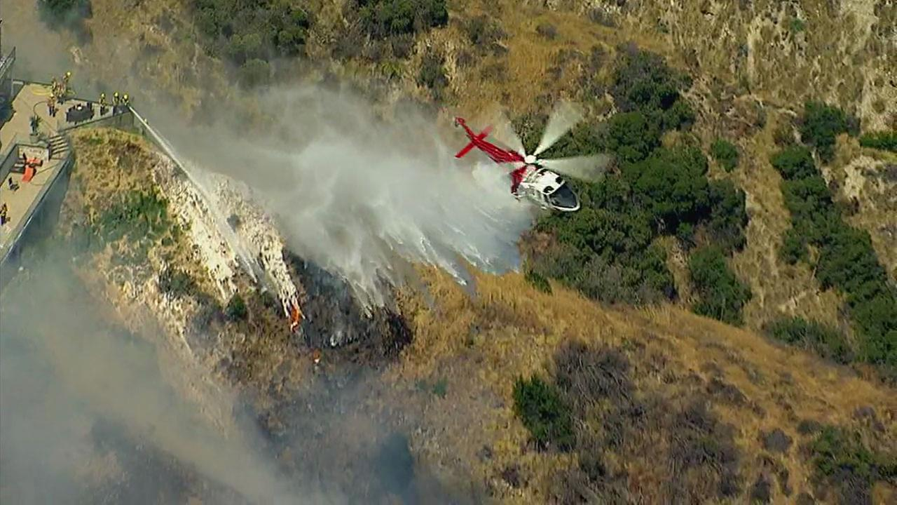 A helicopter drops water on a brush fire burning in the hillsides of Burbank on Wednesday, June 28, 2017.KABC