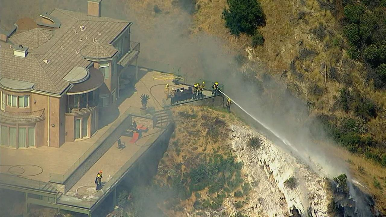 Firefighters protected a home from a brush fire in Burbank on Wednesday, June 28, 2017.KABC