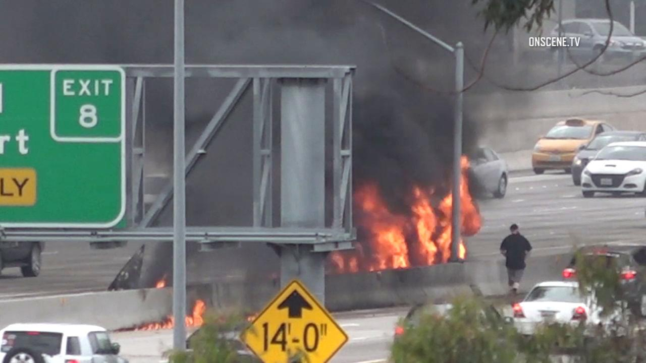 Fire rises from a twin-engine Cessna 310 on the 405 Freeway after it crashed down on Friday, June 30, 2017.