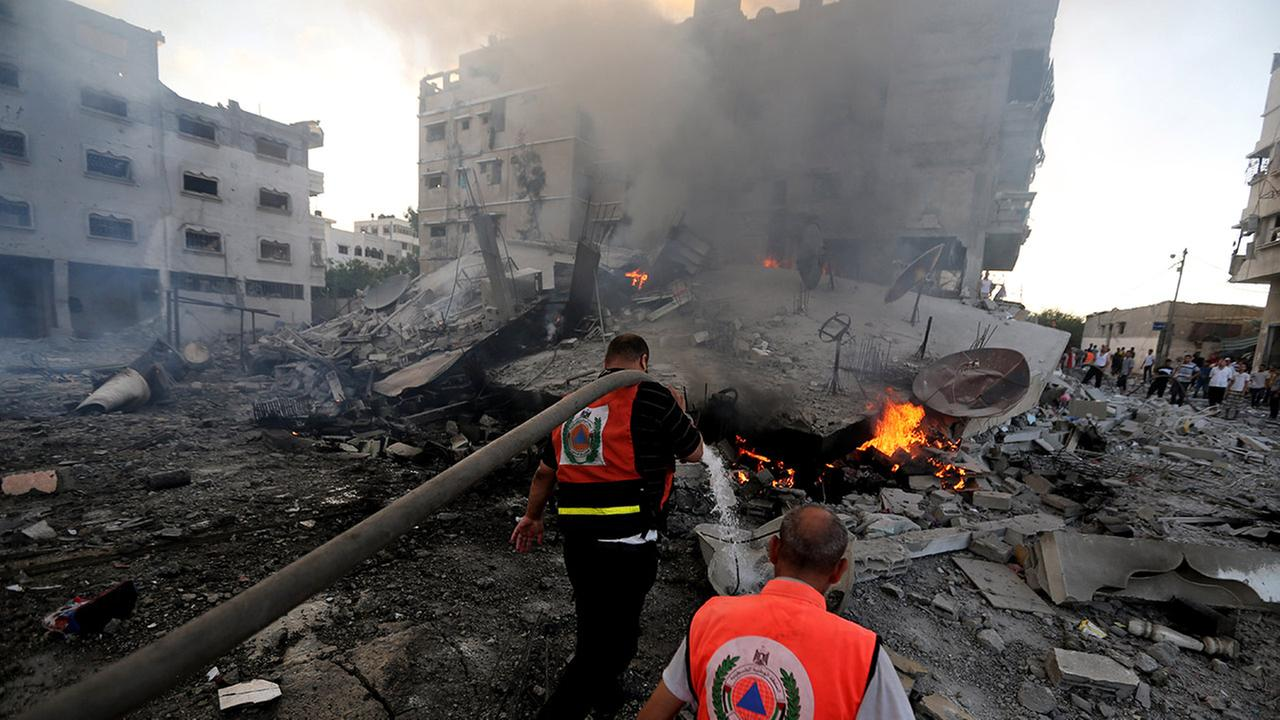 Palestinian firefighters try to extinguish flames in an area damaged in an Israeli airstrike in Gaza City in the Gaza Strip on Thursday, July 24, 2014.
