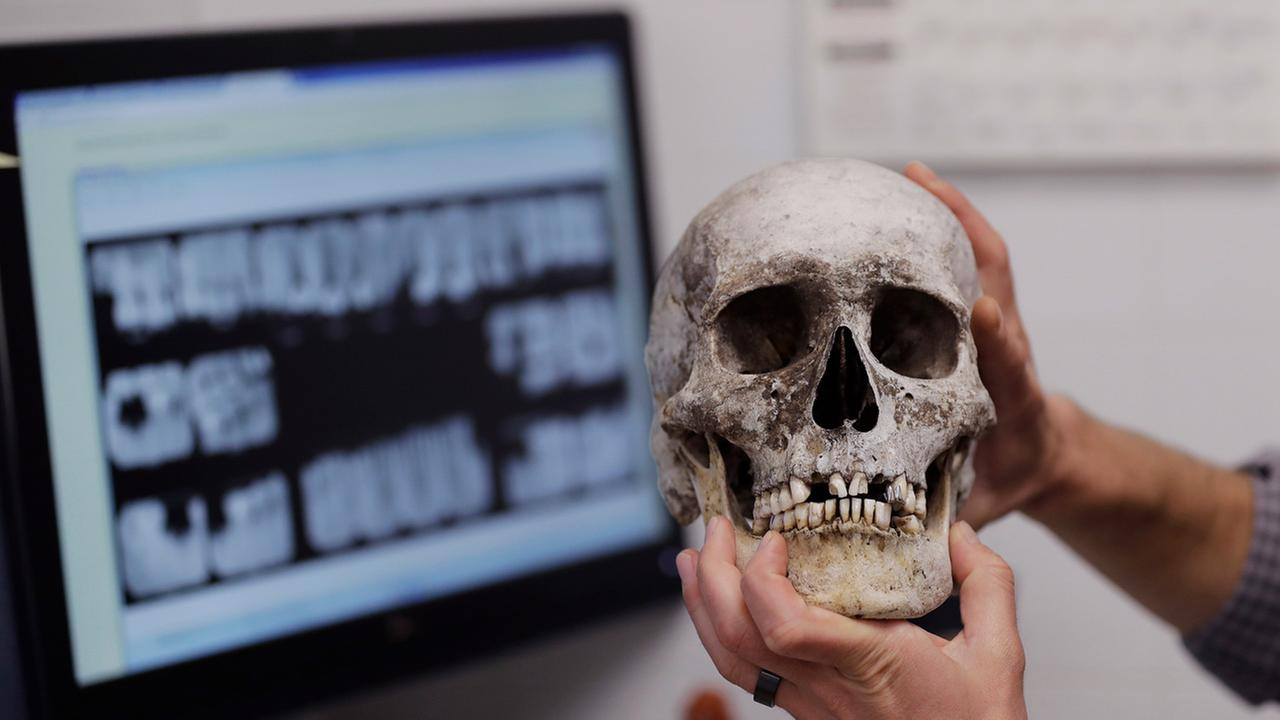 In this Wednesday, April 12, 2017, photo, Dr. Tim Gocha uses dental records as he works to help identify the remains of immigrant who died along the U.S-Mexico border.