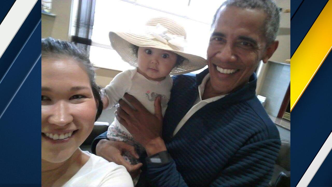 In this July 3, 2017 photo provided by Jolene Jackinsky, former U.S. President Barack Obama holds Jackinskys 6-month-old baby girl while posing for a selfie with the pair.