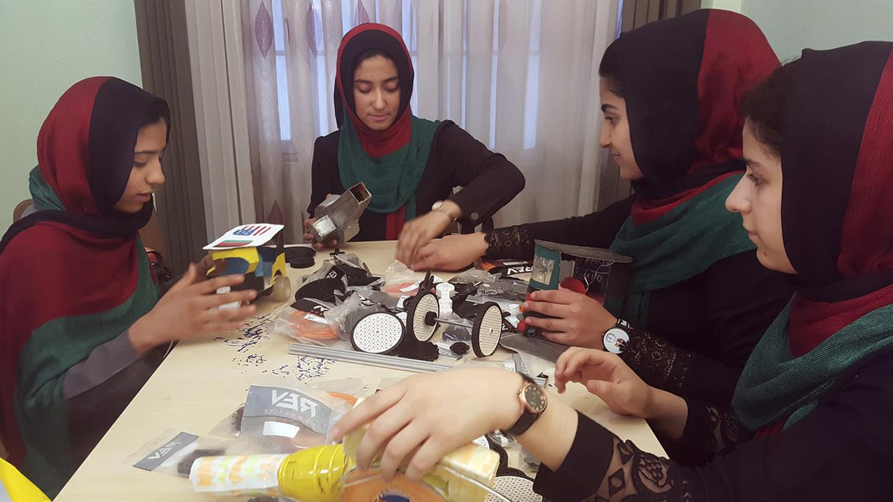 In this Thursday, July 6, 2017 photo, teenagers from the Afghanistan Robotic House, a private training institute, practice at the Better Idea Organization center in Afghanistan.
