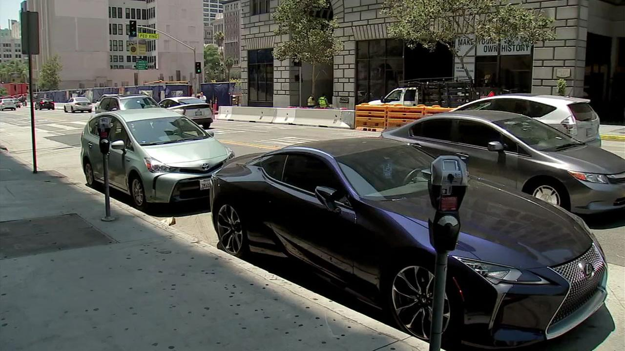 Two cars are parked along a curb near meters in Los Angeles.