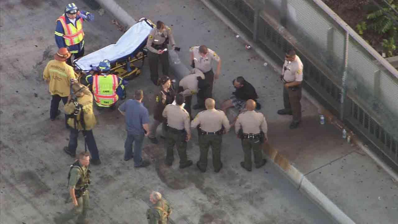 A man who was seen clinging to a freeway sign attached to an overpass above the 5 Freeway in East Los Angeles was taken into custody July 25, 2014.
