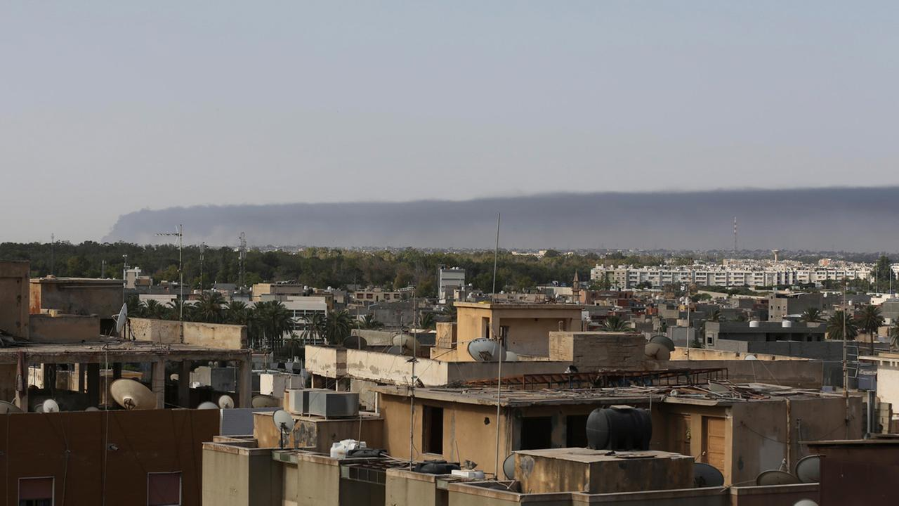 Smoke rises on the horizon in Tripoli, Libya, early Sunday, July 13, 2014.