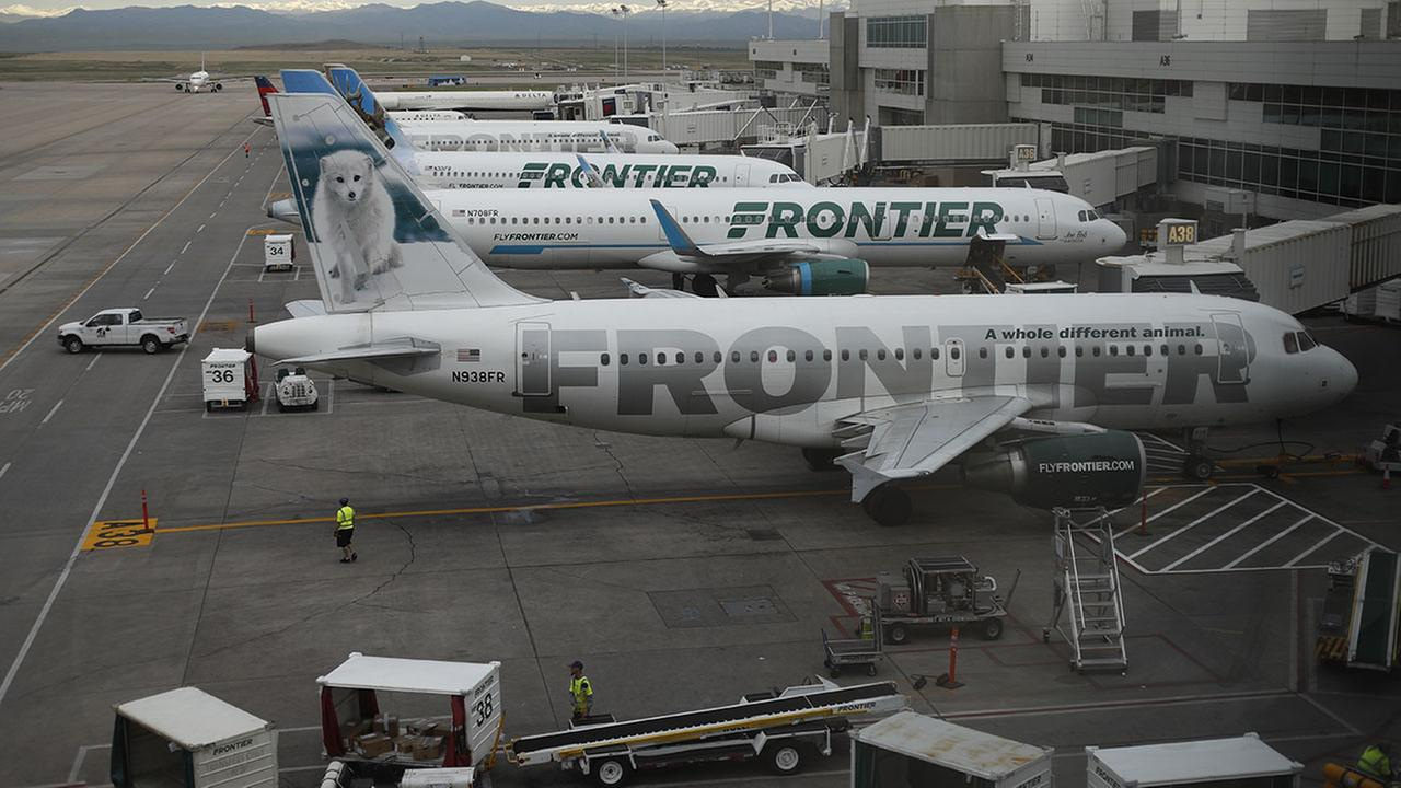 In this Monday, May 15, 2017, photograph, Frontier Airlines jetliners sit at gates on the A concourse at Denver International Airport.
