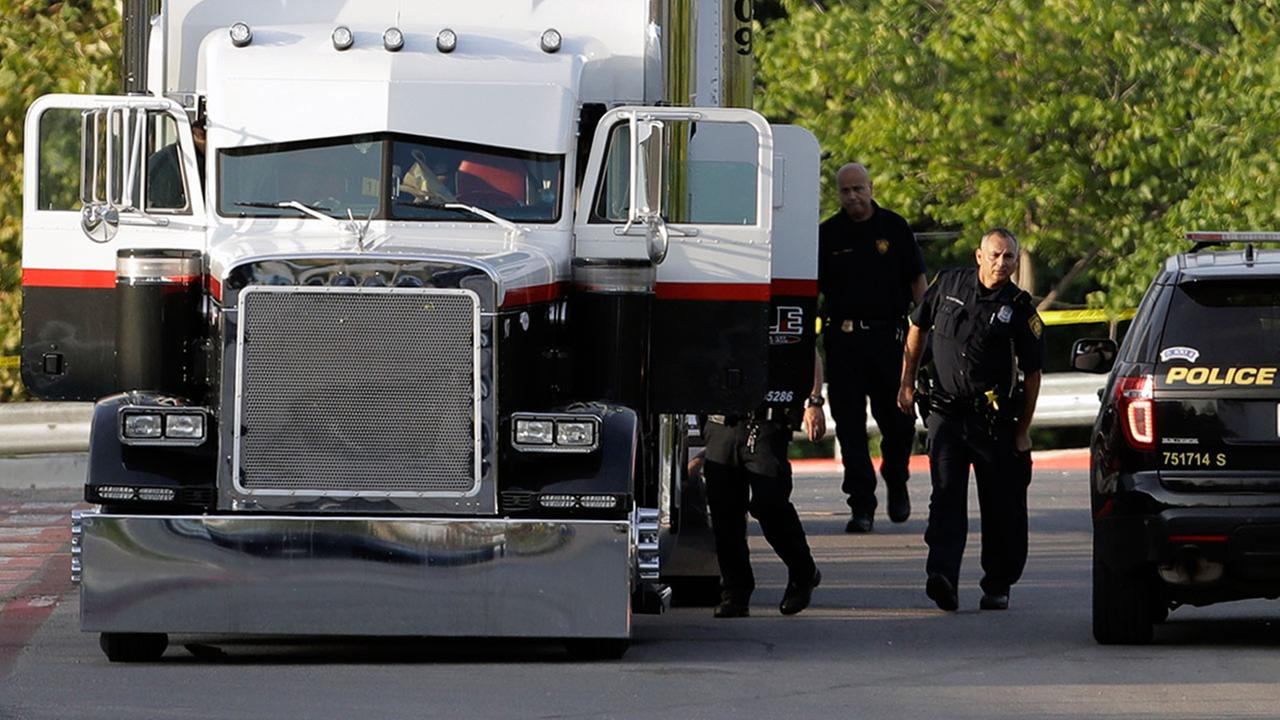 Police investigate the scene where eight people were found dead in a tractor-trailer outside a Walmart store Sunday, July 23, 2017, in San Antonio.