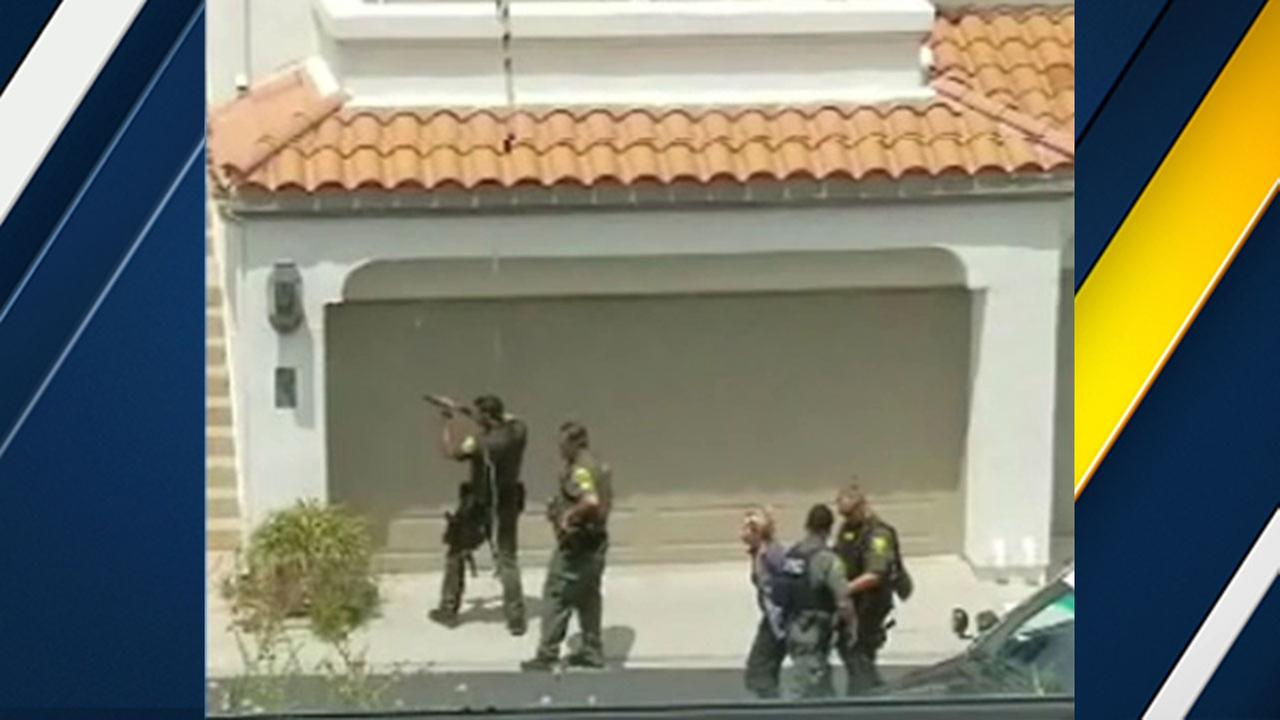 Orange County sheriffs deputies assist a woman who left a home in Dana Point where a gunshot was reported.