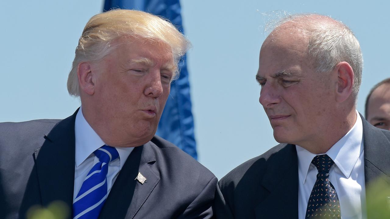 President Donald Trump talks with Homeland Security Secretary John Kelly during commencement at the U.S. Coast Guard Academy in New London, Conn., Wednesday, May 17, 2017.