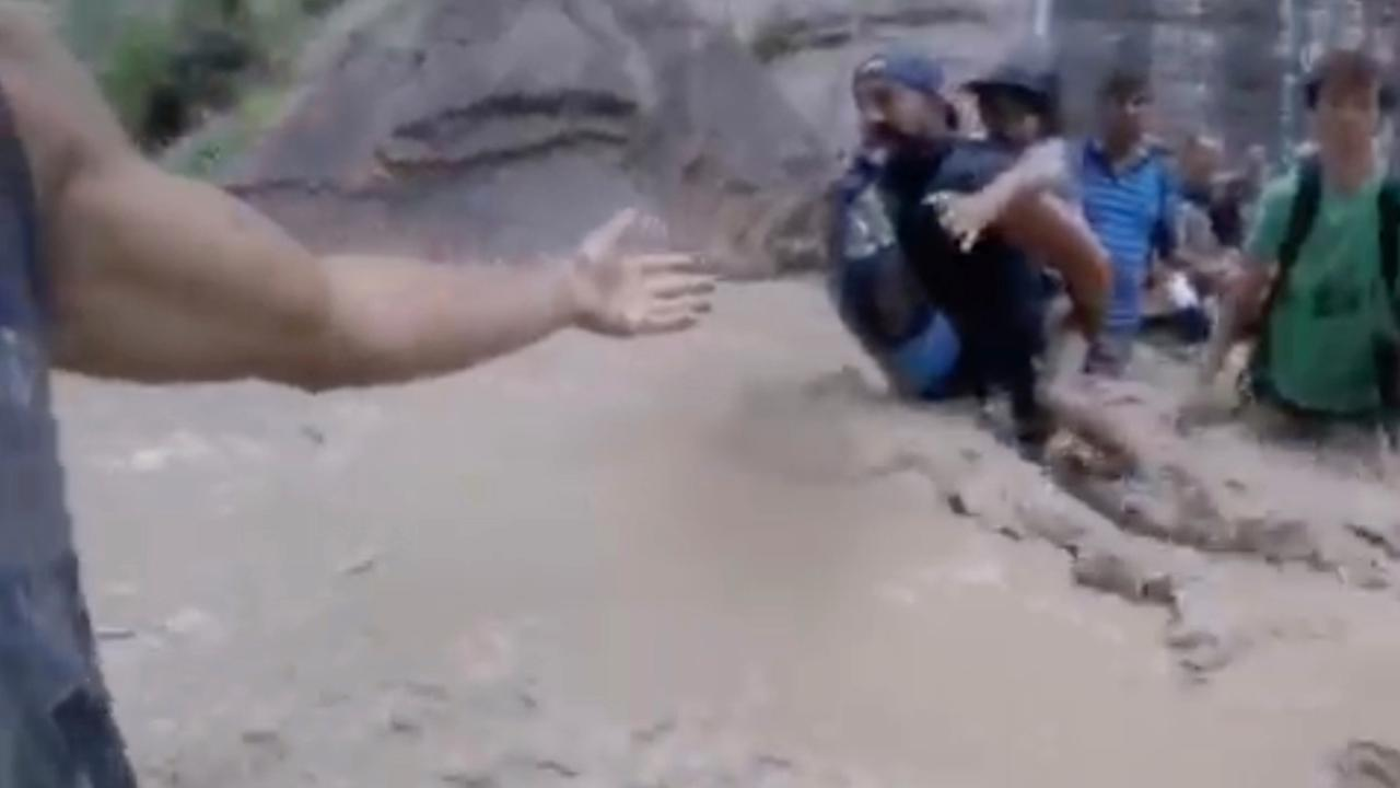 In this July 29, 2017, image made from a video provided by Jhonatan Gonzalez, shows hikers forming a human chain to cross a river swollen with flash flood waters.