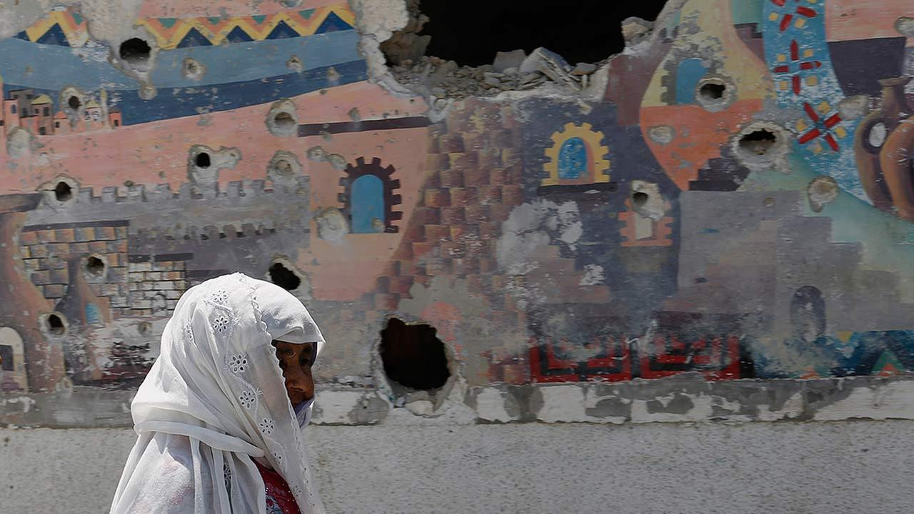 A woman walks past the damaged wall of a building outside the Abu Hussein U.N. school after an Israeli strike on Wednesday, July 30, 2014.