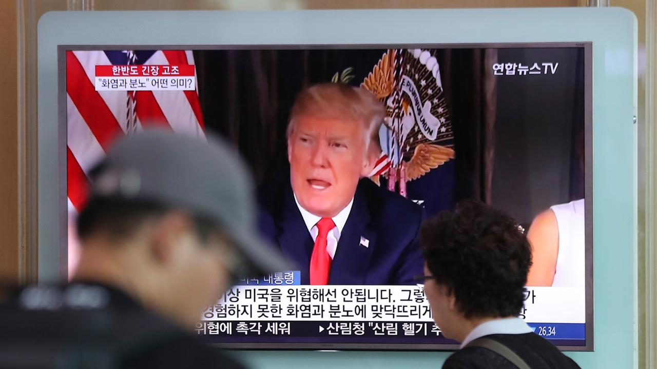 People walk by a TV screen showing a local news program reporting with an image of U.S. President Donald Trump at the Seoul Train Station in Seoul, South Korea.