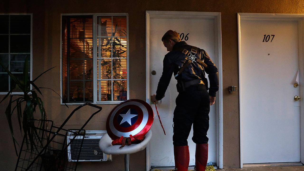 In this Monday, May 8, 2017 photo, Captain America impersonator Henry Hodge, a cinematographer from England, opens his apartment door in Los Angeles.Jae C. Hong