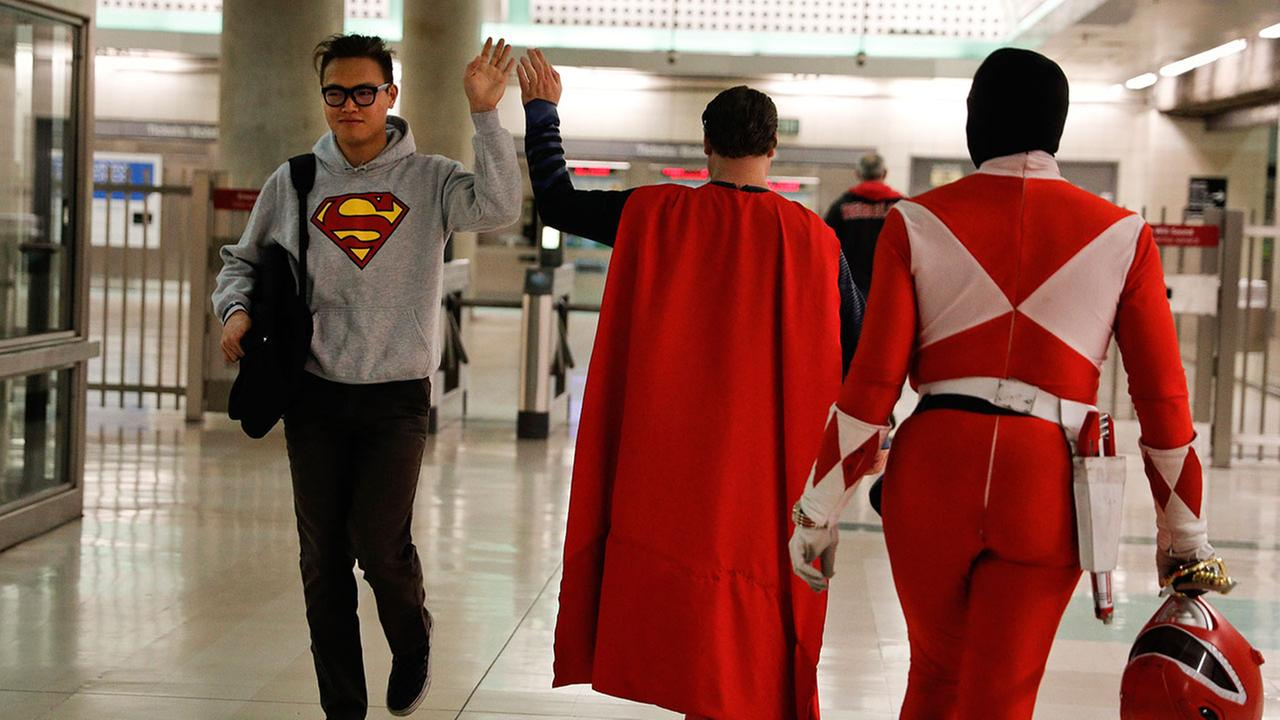 In this Tuesday, May 16, 2017 photo, Superman impersonator Justin Harrison high-fives a commuter as he and his roommate head back home after working on Hollywood Boulevard.Jae C. Hong