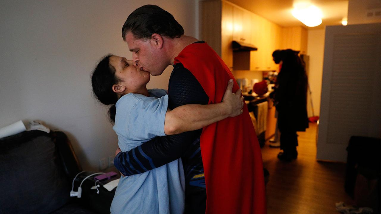 In this Tuesday, May 16, 2017 photo, wearing a Superman costume, Justin Harrison kisses his wife in their apartment before heading out to Hollywood Boulevard in downtown L.A.Jae C. Hong